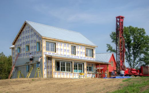Installing siding and drilling for water