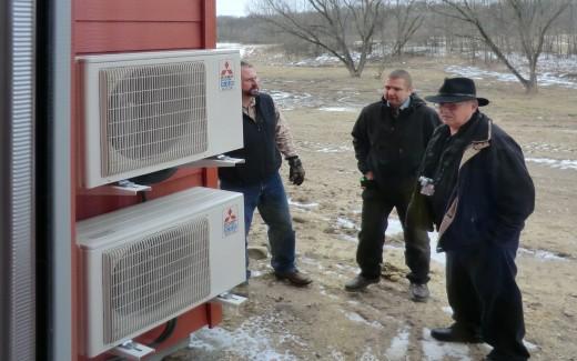 Mitsubishi representatives examining outdoor units